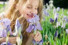 Riechende Blume des kleinen Mädchens lizenzfreie stockbilder
