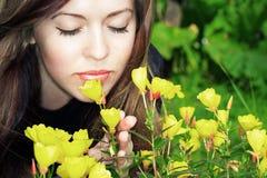 Riechende Blumen der Frau lizenzfreies stockbild