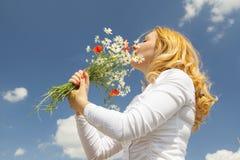 Riechende Blumen der Frau Stockfotos