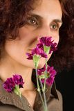 Riechende Blumen der Redheadfrau Lizenzfreies Stockfoto