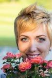 Riechende Blumen der wirklichen Frau draußen Lizenzfreies Stockfoto
