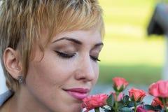 Riechende Blumen der wirklichen Frau draußen Stockbilder