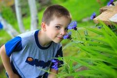 Riechende Blumen des Jungen Lizenzfreies Stockbild