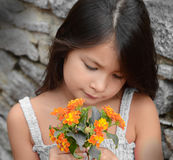 Riechende Blumen des jungen Mädchens Stockbild