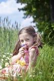 Riechende Blumen des jungen Mädchens Lizenzfreies Stockbild