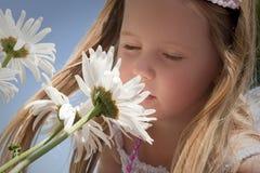 Riechende Blumen des kleinen Mädchens Lizenzfreie Stockfotos