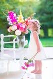 Riechende Blumen des kleinen Mädchens zu Hause Stockfotos