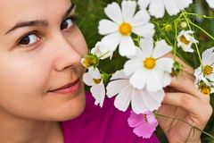 Riechende Blumen des Mädchens Stockfoto