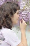 Riechende Blumen des Mädchens Stockfotos