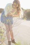 Riechende Blumen des ruhigen Hippie-Mädchens Lizenzfreie Stockfotos