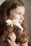 Riechende Gänseblümchen des kleinen Mädchens lizenzfreie stockfotos