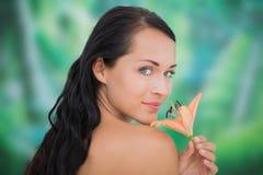 Riechende Lilie des schönen nackten Brunette Stockbilder