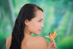 Riechende Lilie des schönen nackten Brunette Lizenzfreie Stockfotografie