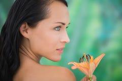 Riechende Lilie des schönen nackten Brunette Lizenzfreie Stockfotos