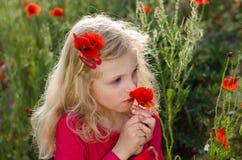 Riechende Mohnblumenblumen des blonden Mädchens Lizenzfreie Stockfotos