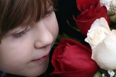 Riechende Rosen des Mädchens Lizenzfreie Stockfotografie