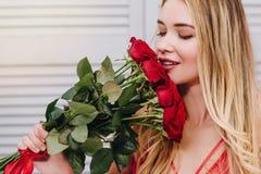 Riechender Blumenstrauß der Frau von roten Rosen lizenzfreie stockfotografie