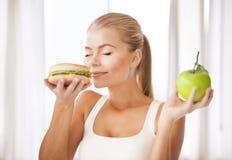 Riechender Hamburger der Frau und halten Apfel Stockfotografie