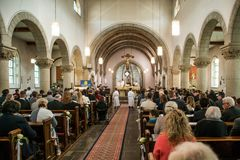 Rieden Germany 15.04.2018 Priest holding church service in front of crowd in theinterior of a church. Rieden Germany 15.04.2018 - Priest holding church service stock images