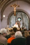 Rieden Germany 15.04.2018 Priest holding church service in front of crowd in theinterior of a church. Rieden Germany 15.04.2018 - Priest holding church service stock photos