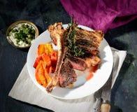 Riedlapje vlees met aromatische kruiden op een plaat met groenten en saus, uitstekende mes en vork op een servet op de donkere ac Stock Foto's