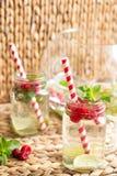 Riegue con las frambuesas, la cal, el hielo y la menta en fondo rústico limonada Foto de archivo