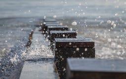 Riegue de la onda que salpica sobre rompeolas en bahía Imagenes de archivo
