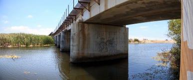 Riegue debajo del puente de la pista de ferrocarril que lleva abajo al océano Fotografía de archivo libre de regalías