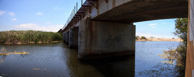 Riegue debajo del puente de la pista de ferrocarril que lleva abajo al océano Imágenes de archivo libres de regalías