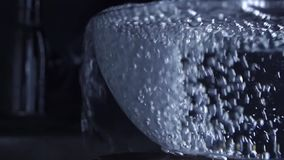 Riegue del golpecito de agua que desborda un bol de vidrio, vídeo de la cámara lenta