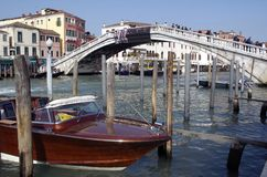 Riegue el barco del taxi por el puente de Rialto en Venecia Imagen de archivo libre de regalías