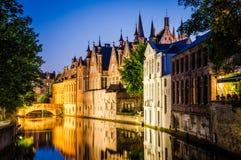 Riegue el canal y las casas medievales en la noche en Brujas Imagen de archivo