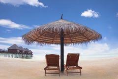 Riegue el chalet con la silla .maldives del paraguas y de playa Imagenes de archivo