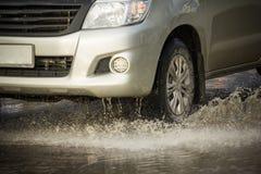 Riegue el chapoteo con el coche en el camino inundado después de lluvias fotos de archivo libres de regalías