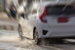 Riegue el chapoteo con el coche en el camino inundado después de lluvias Foto de archivo