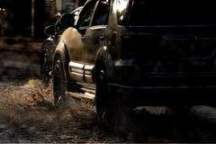 Riegue el chapoteo con el coche en el camino inundado después de lluvias fotografía de archivo libre de regalías