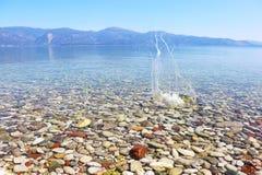 Riegue el chapoteo en el agua cristalina de Peloponeso Grecia fotografía de archivo