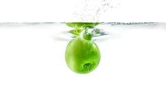 Riegue el chapoteo Manzana verde debajo del agua La burbuja de aire y transparen Imagen de archivo libre de regalías