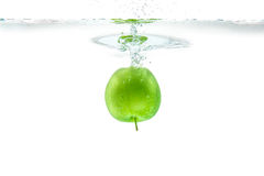 Riegue el chapoteo Manzana verde debajo del agua La burbuja de aire y transparen Foto de archivo libre de regalías
