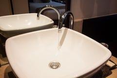 Riegue el descenso del grifo, agua dulce en cuarto de baño Imagenes de archivo