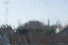 Riegue el descenso sobre el vidrio fuera de la ventana, fondo de las casas Imágenes de archivo libres de regalías
