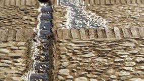 Riegue el funcionamiento abajo de un canal del amarrar en las calles de Frigiliana Imagenes de archivo