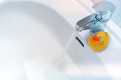 Riegue el funcionamiento de un grifo en un fregadero blanco con un pato de goma Fotos de archivo libres de regalías