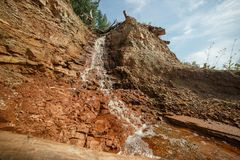 Riegue el funcionamiento en una corriente abajo de la suciedad brillante de la arcilla roja de la cascada del bosque del taiga Foto de archivo libre de regalías