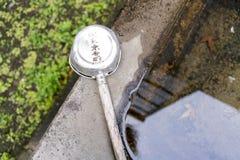 Riegue el lavabo y la cucharón en la capilla sintoísta en Tokio, Japón Fotos de archivo libres de regalías