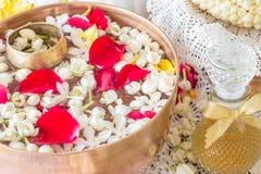 Riegue en el cuenco mezclado con perfume y flores Imágenes de archivo libres de regalías