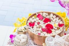 Riegue en el cuenco mezclado con perfume y flores Foto de archivo libre de regalías