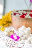Riegue en el cuenco mezclado con perfume y flores Imagenes de archivo
