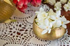 Riegue en el cuenco mezclado con perfume y flores Fotos de archivo