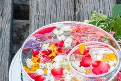 Riegue en el cuenco mezclado con perfume y flores Fotografía de archivo libre de regalías